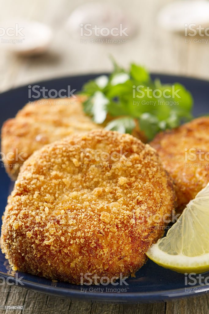 Crab cakes on a blue plate with lemon wedge stock photo