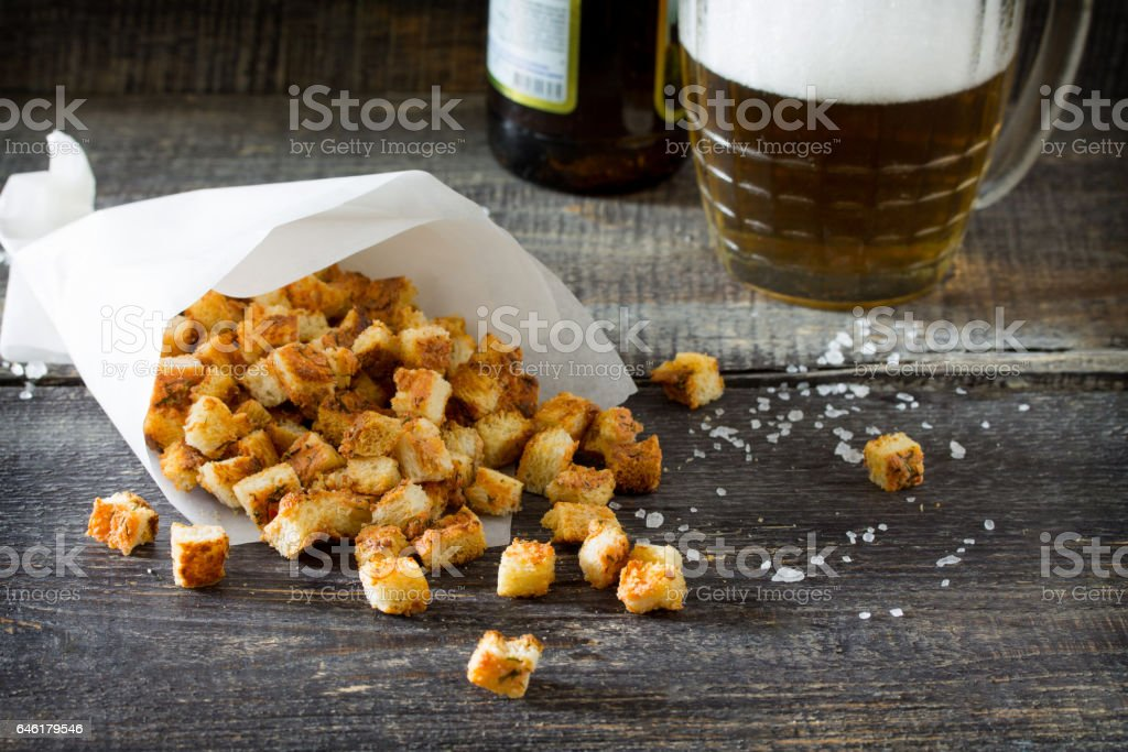 Crab croutons in a paper bag on a wooden table. Snack food to beer. stock photo