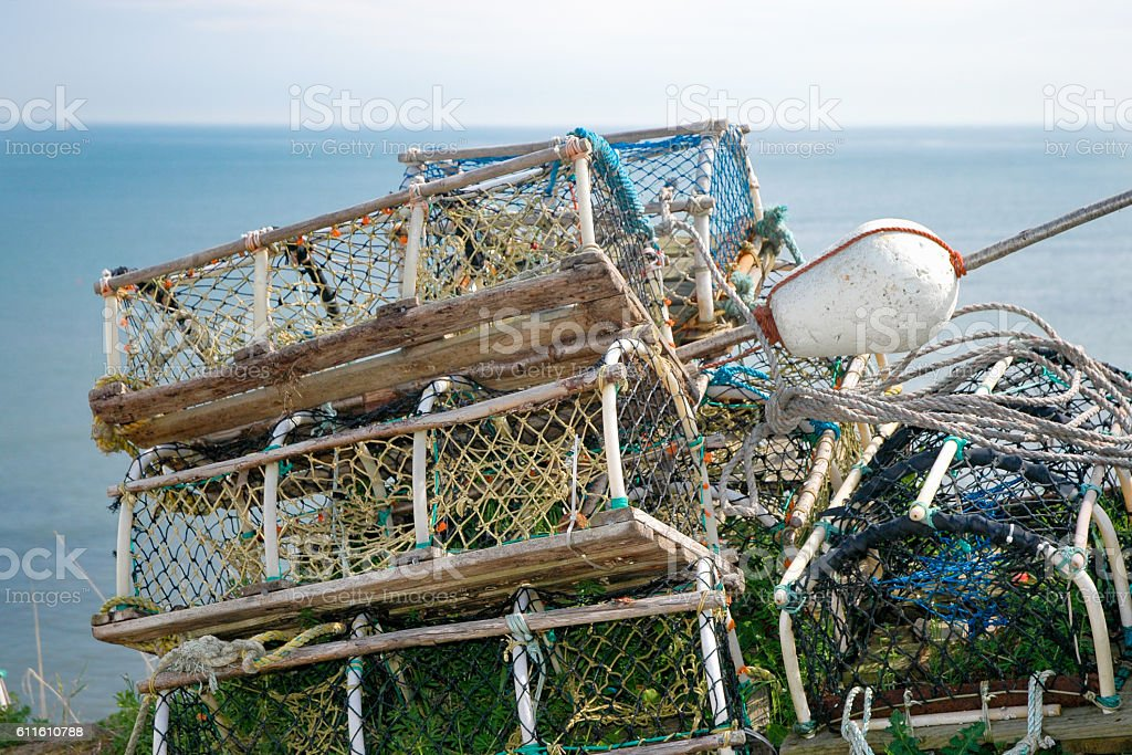 Crab pots stacked on a harbour front in England stock photo
