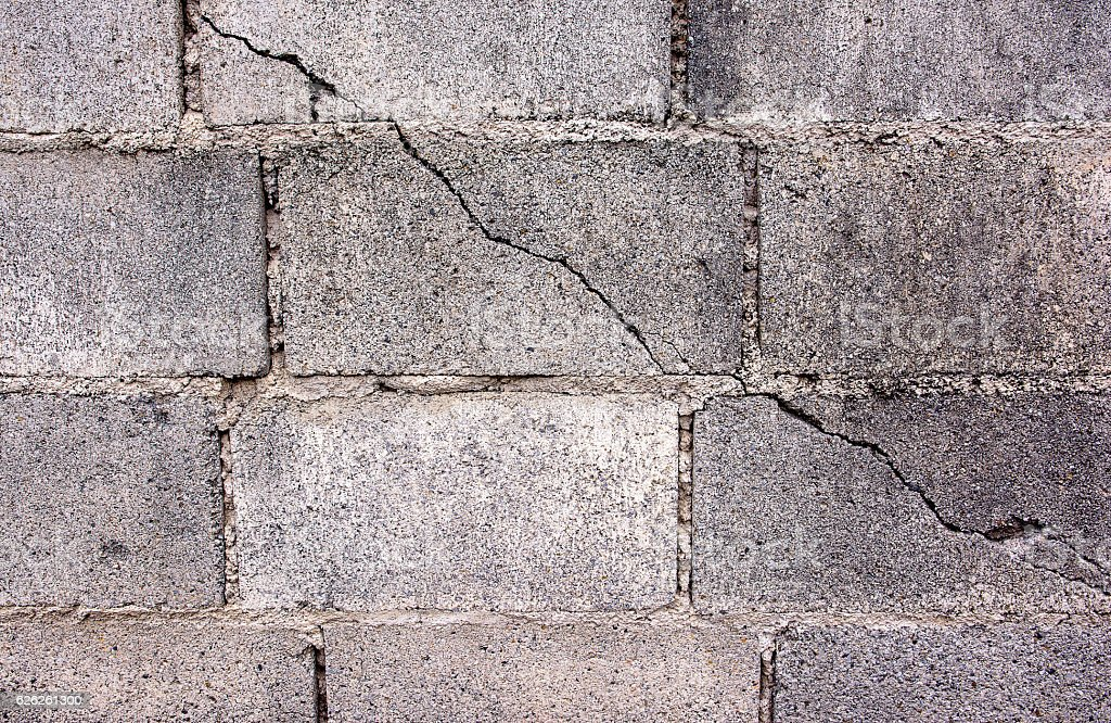 Crack in concrete cinder block wall background.Cement cinder block stock photo