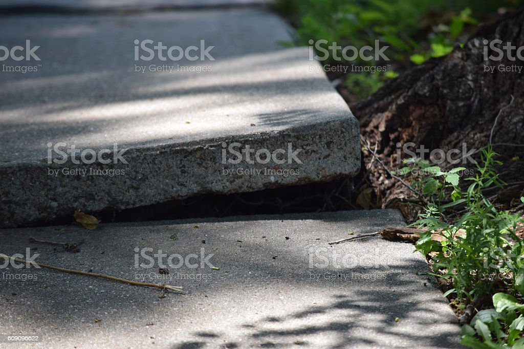 cracked and broken sidewalk in need of repair stock photo