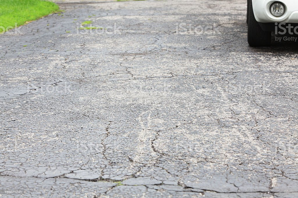 Cracked asphalt driveway with car parked royalty-free stock photo