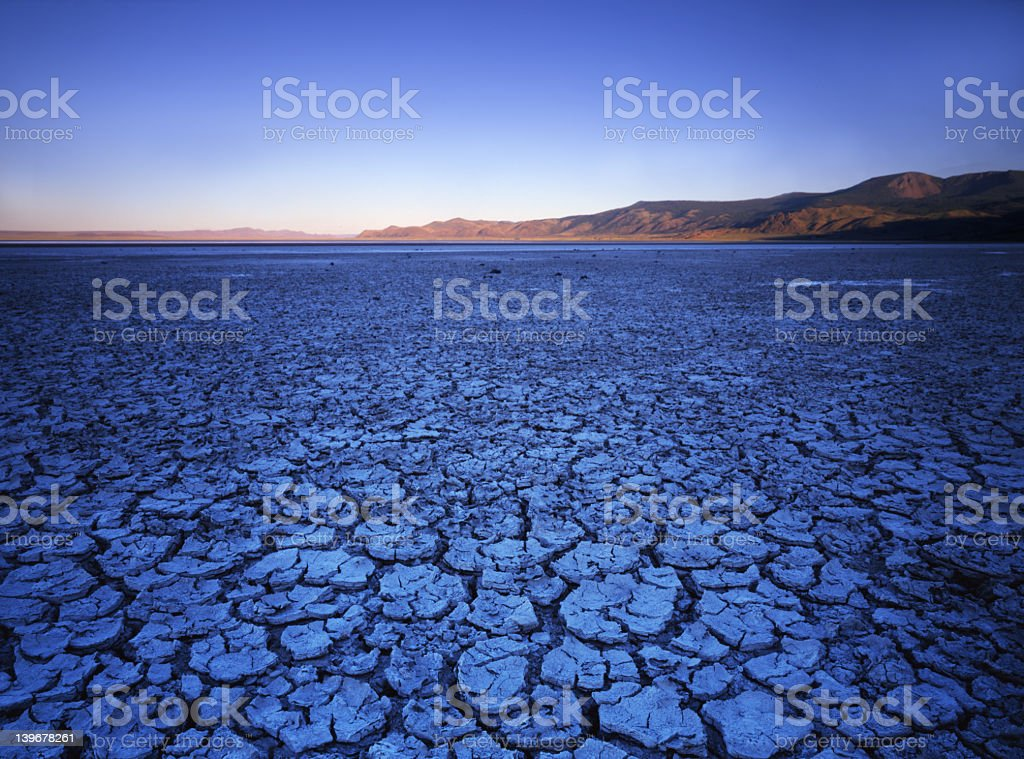 Cracked blue earth in the desert with the mountains in view royalty-free stock photo