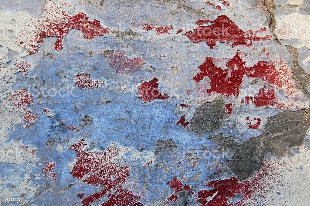 Cracked blue, red and white paint on cement wall stock photo