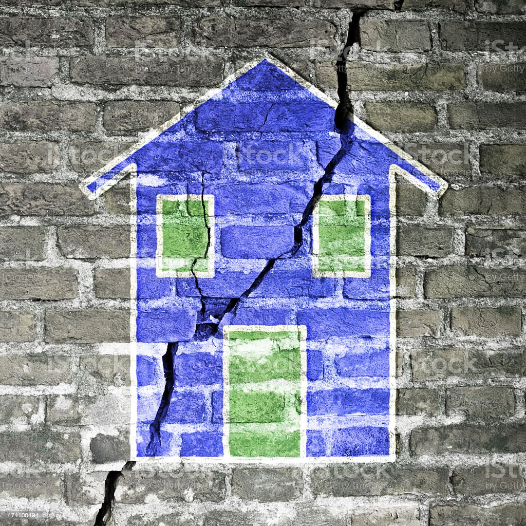 Cracked brick wall with a blue house stock photo