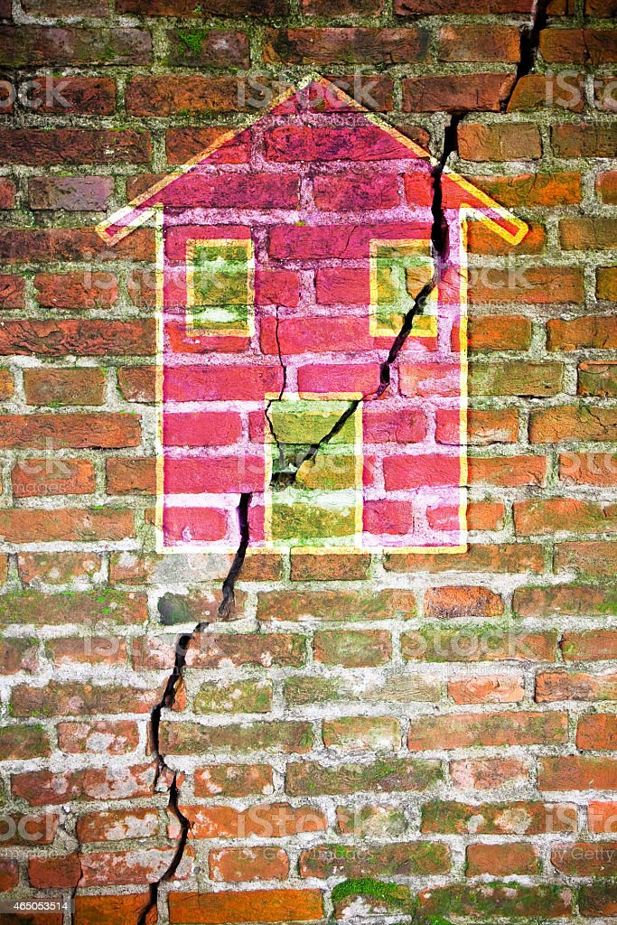 Cracked brick wall with a colored house drawn on it stock photo