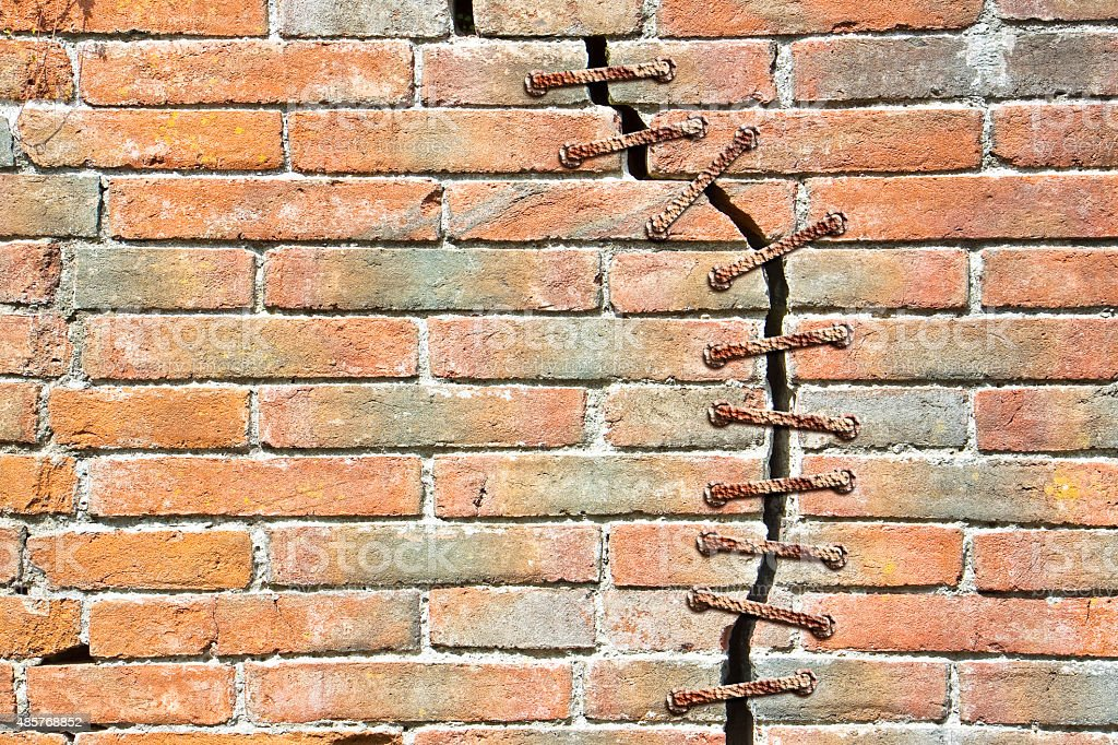 Cracked brick wall with a metal seam stock photo