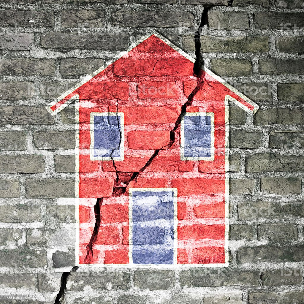 Cracked brick wall with a red house drawn on it stock photo