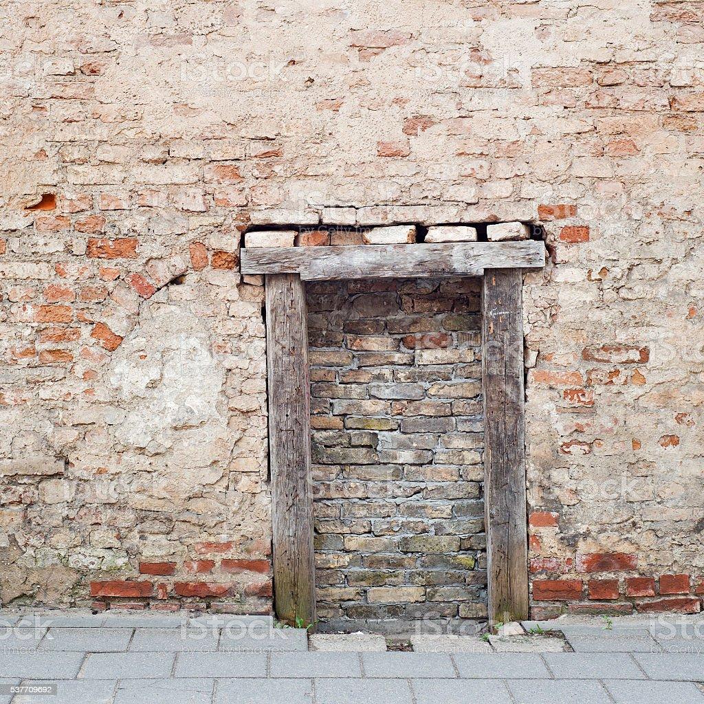 cracked brick wall with bricked up doorway stock photo