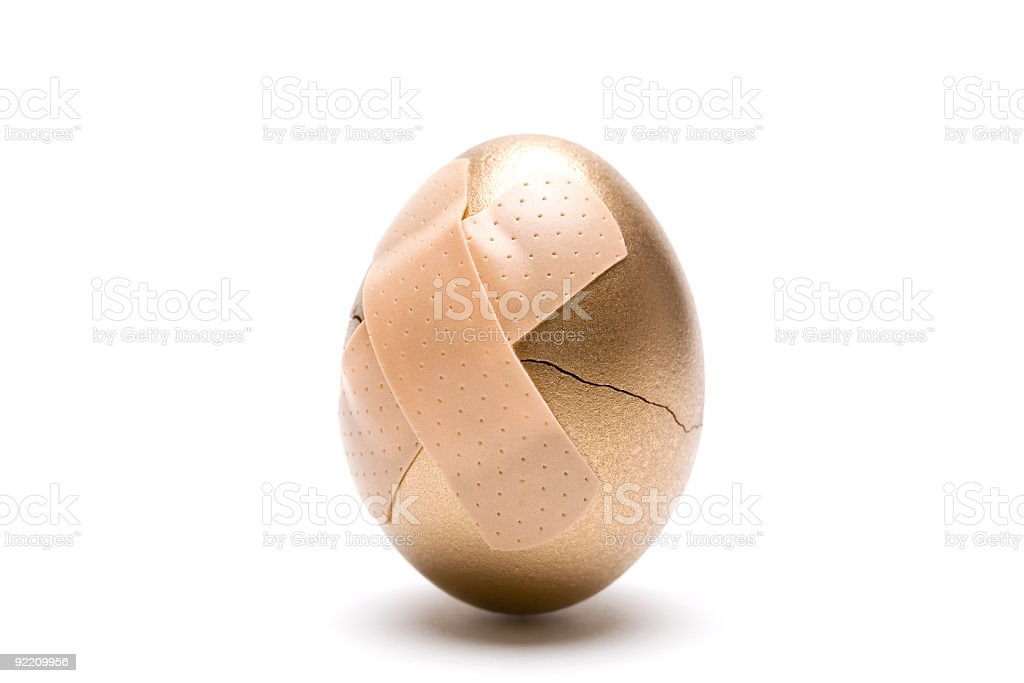 Cracked Golden Egg with Adhesive Bandage royalty-free stock photo