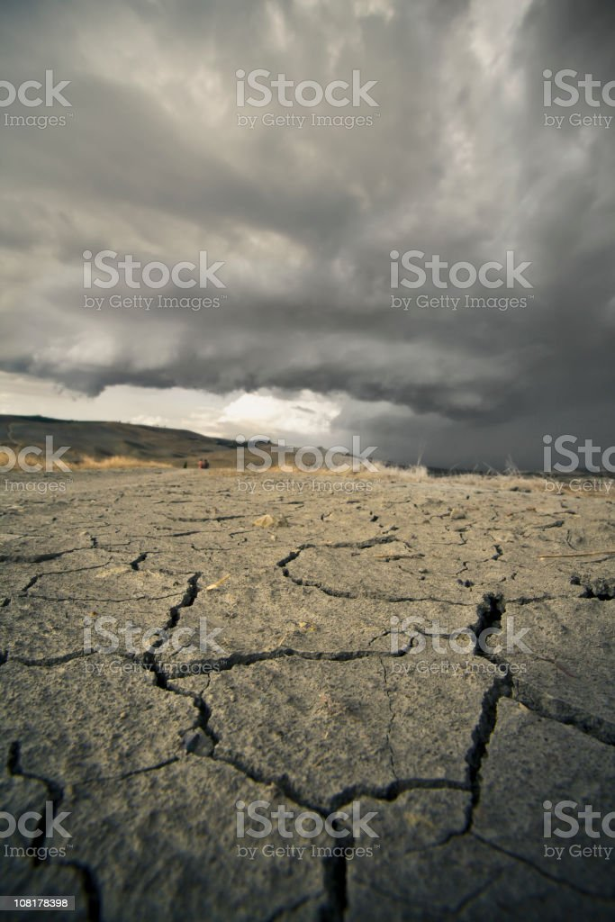 Cracked land with a stormy sky stock photo