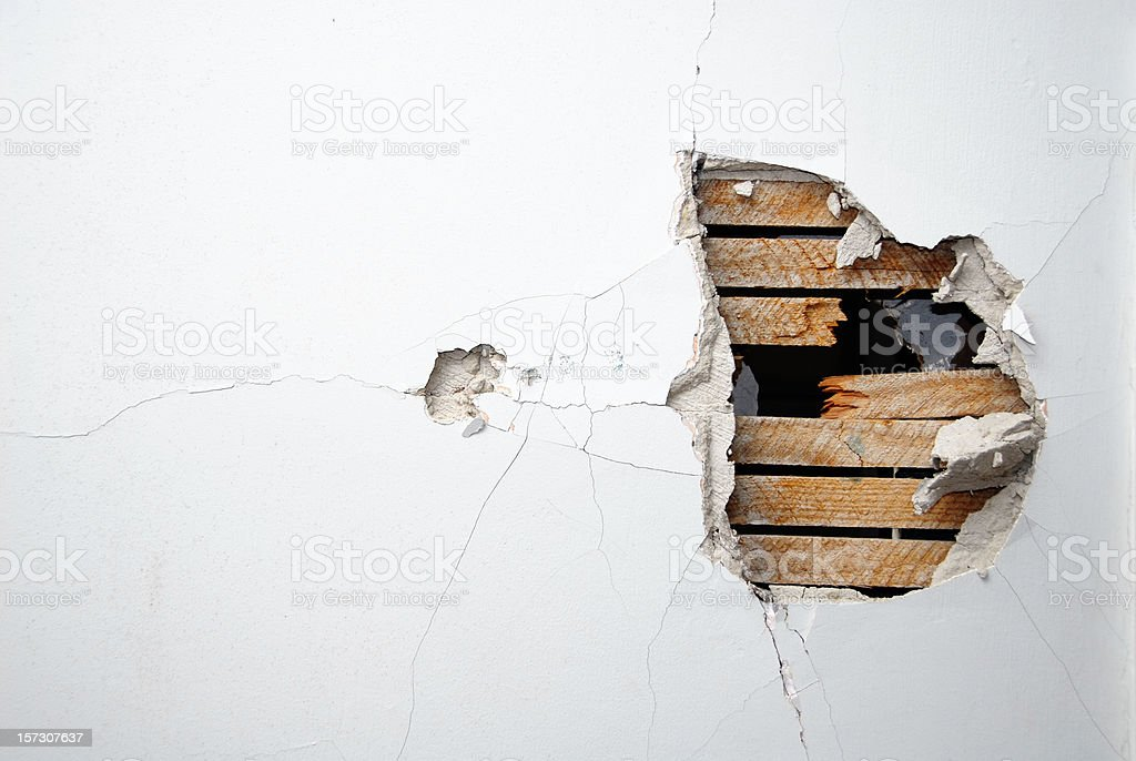 Cracked plaster, drywall and wood of a home's white wall stock photo