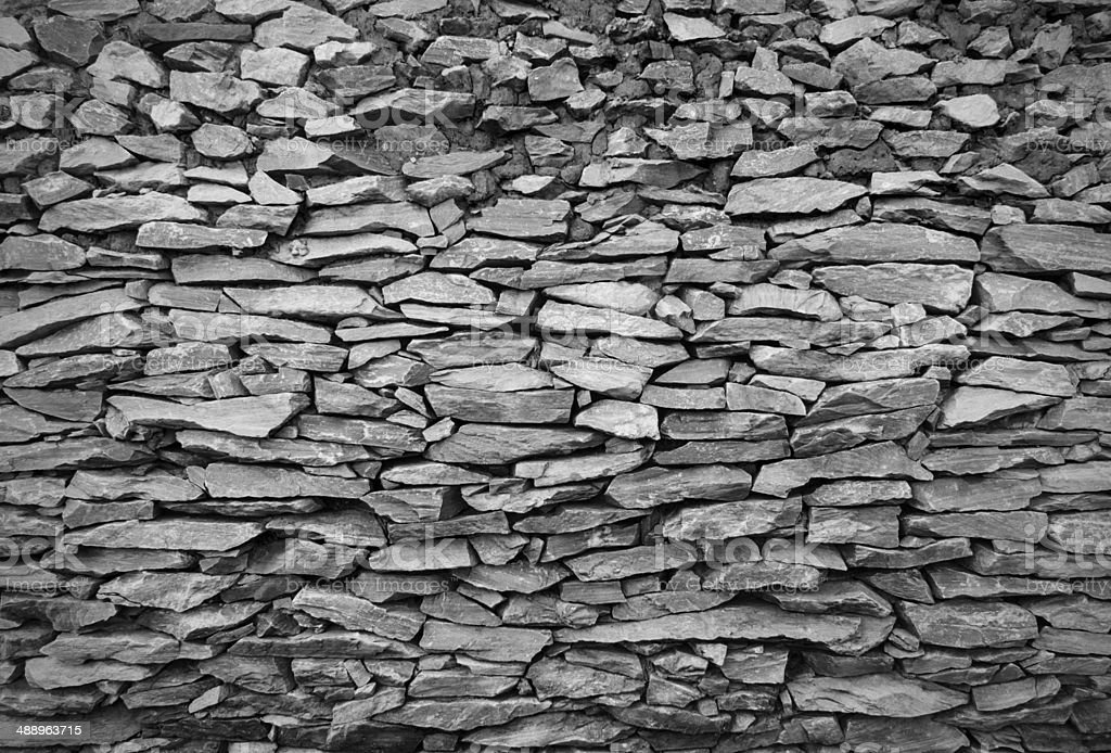 Cracked real stone wall surface with cement royalty-free stock photo
