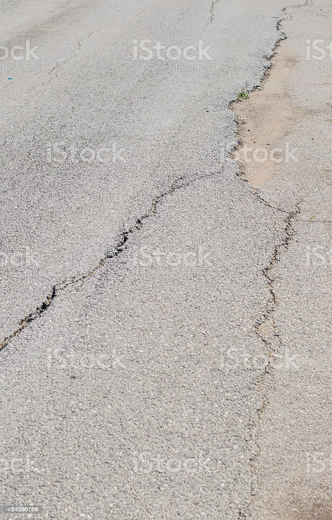 cracked road and potholes in pavement of a city street stock photo