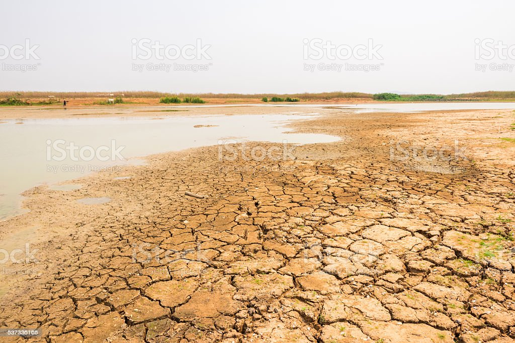 cracked soil in the bottom of a river showing drought stock photo