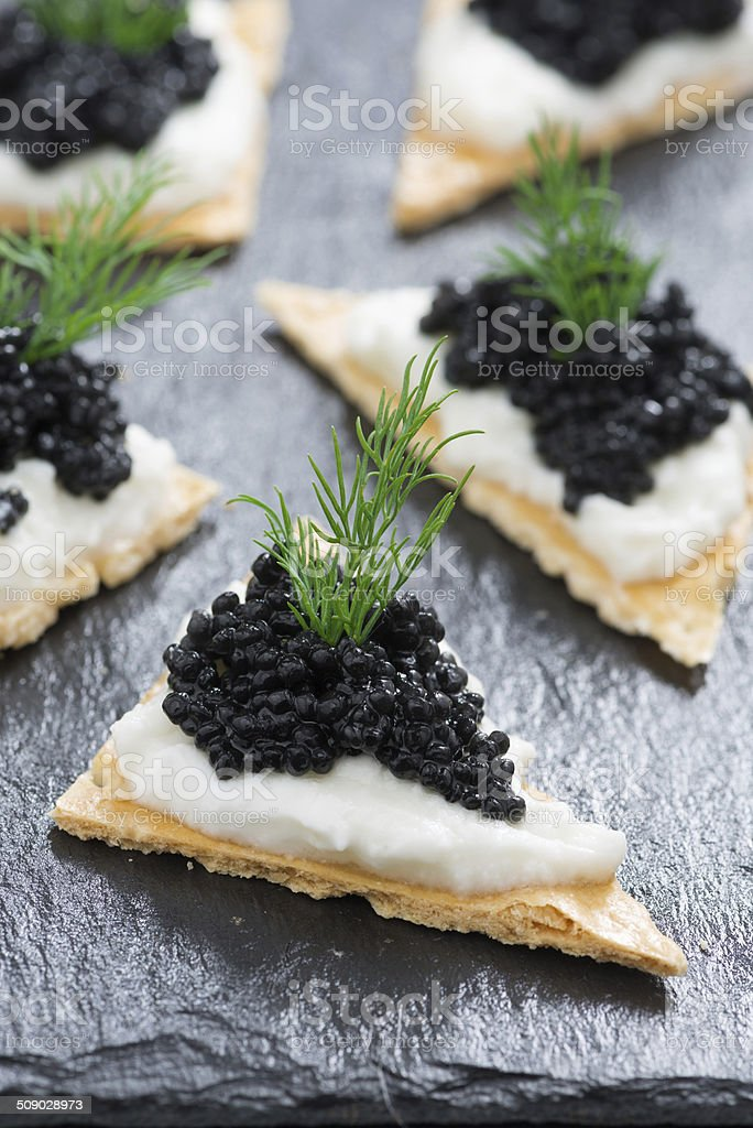 crackers with cream cheese and black caviar, vertical stock photo