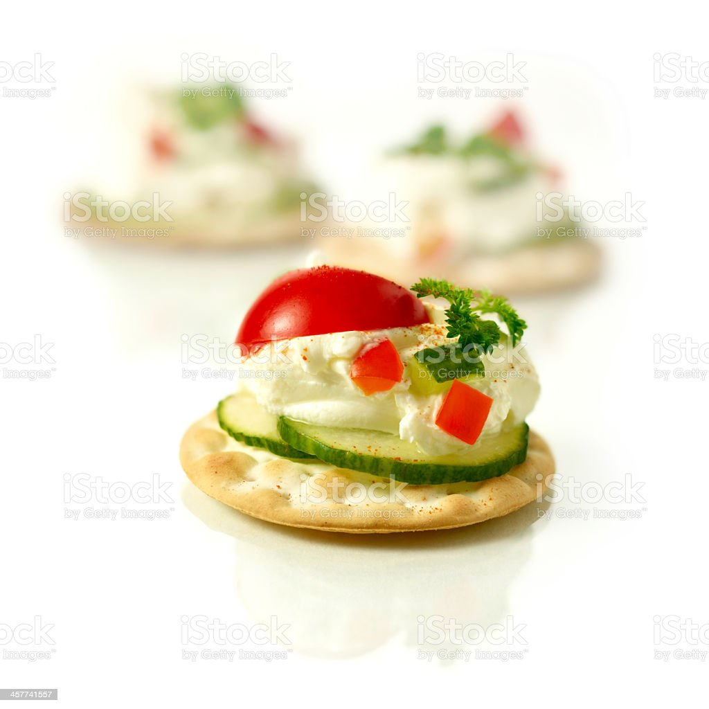 Crackers with cucumbers, dip, and tomatoes on top stock photo