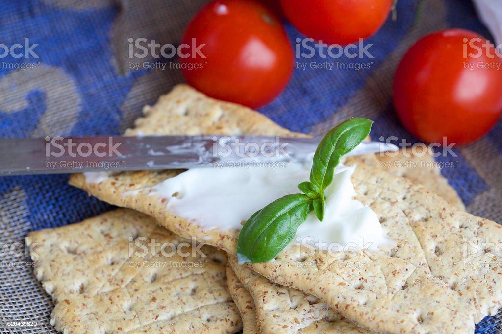 Crackers with stracchino cheese. Closeup. stock photo