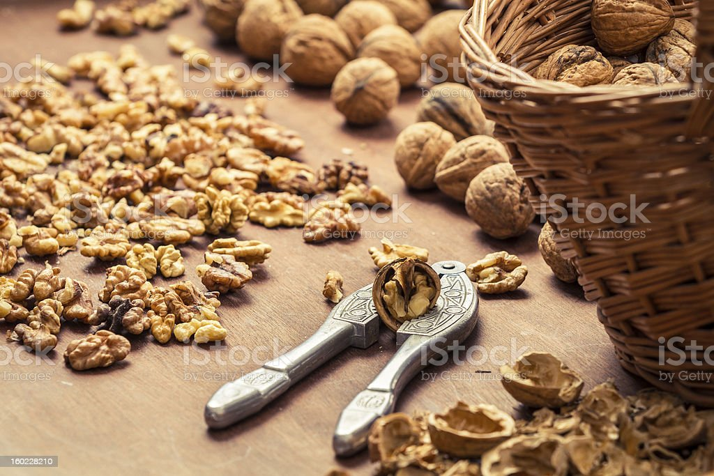 Cracking walnuts on wicker basket royalty-free stock photo