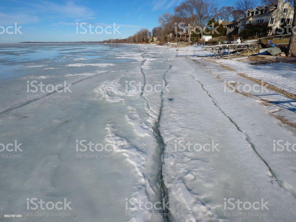 Cracks in the ice along the shoreline stock photo