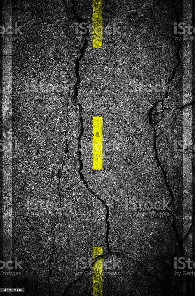 Cracks on asphalt the yellow line dividing lanes stock photo