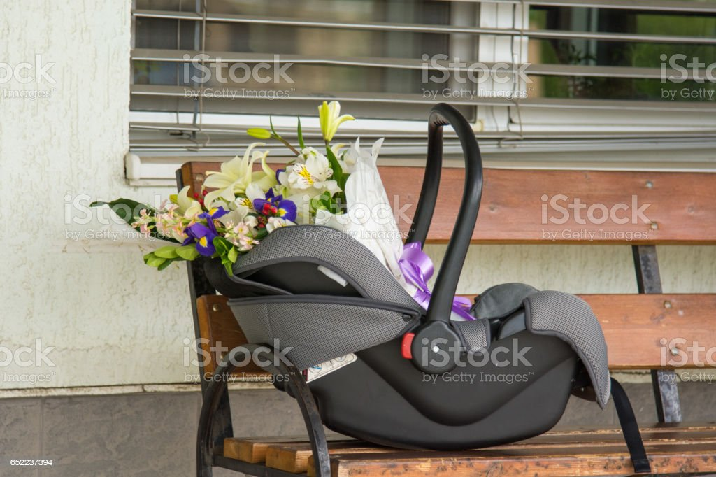 Cradle-carry for children with bouquet of flowers inside stock photo