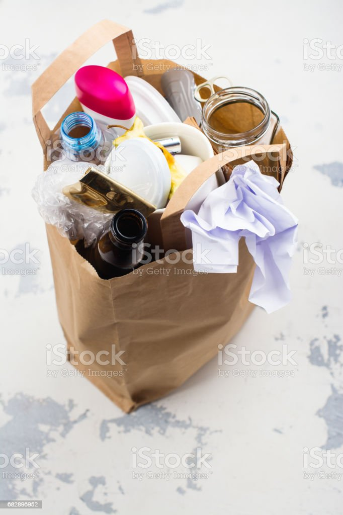 Craft paper bag with unsorted waste on white stone background stock photo