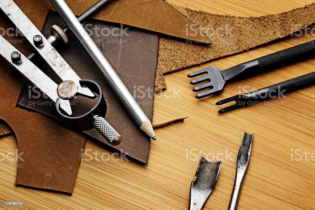 craft tool with fragmented leather on the wooden table stock photo
