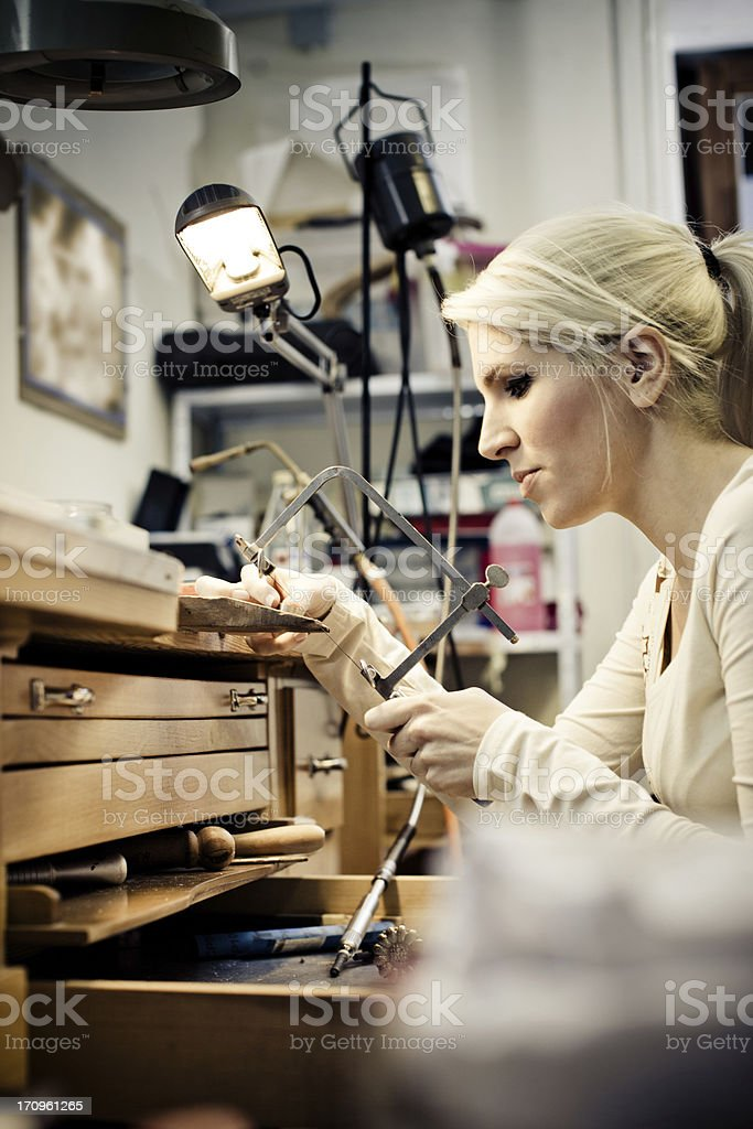 Young woman crafting jewerly in a cozy laboratory