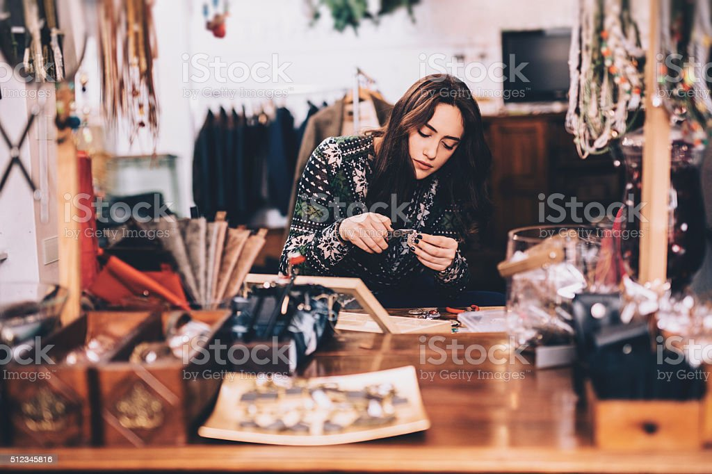 A young woman working on a piece of jewelry