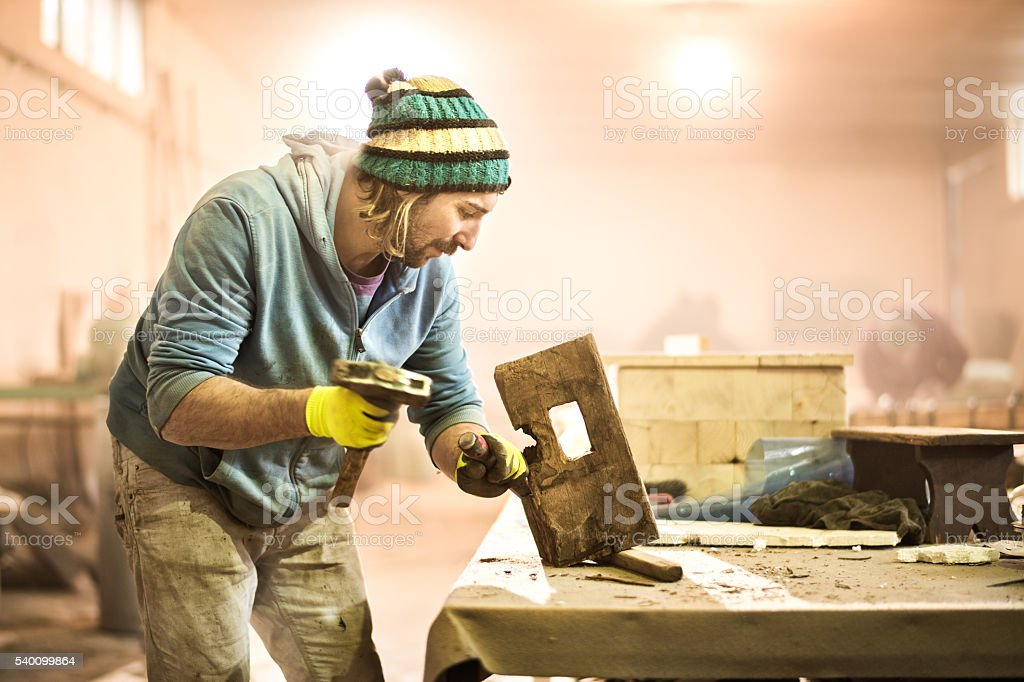 Craftman with hammer and chisel stock photo