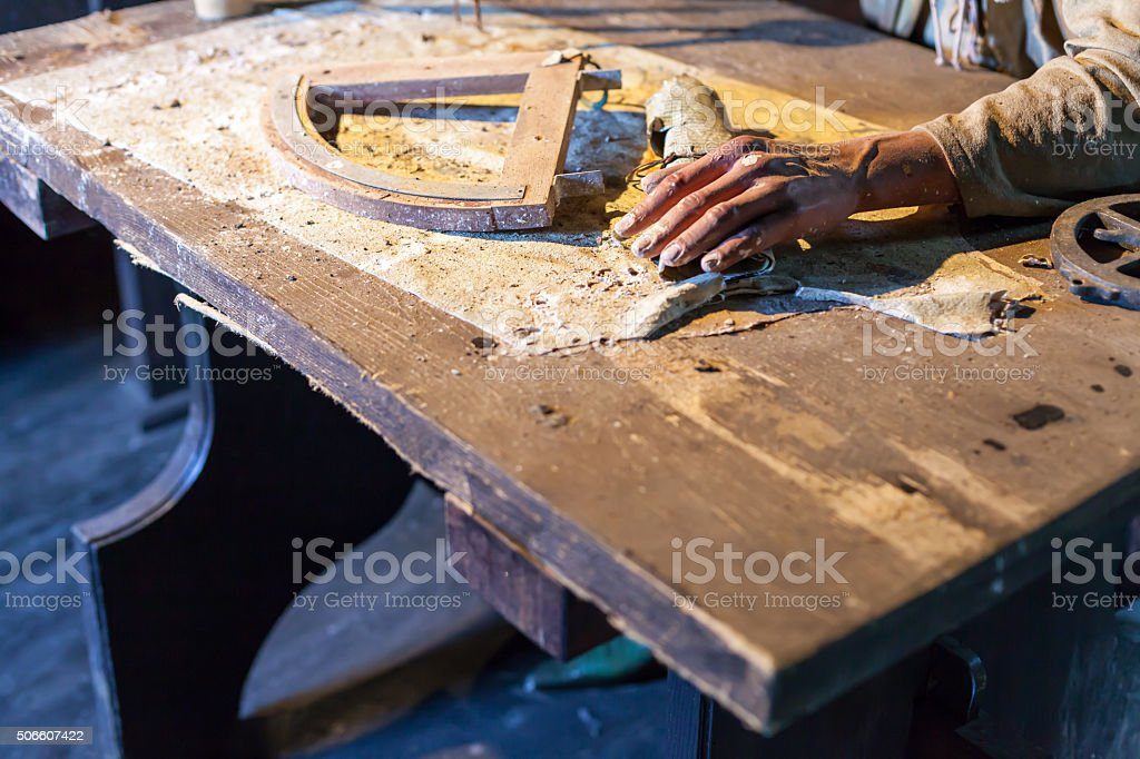 Craftman working while sitting at table. Unrecognizable stock photo