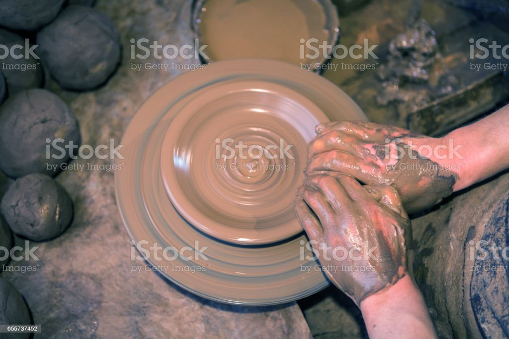 Craftsman artist making craft, pottery, sculptor from fresh wet clay on pottery wheel stock photo