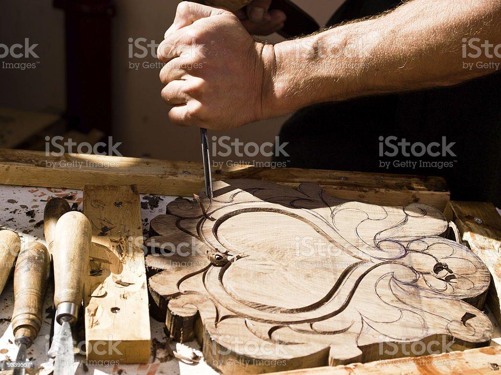 Craftsman carving a souvenir board royalty-free stock photo
