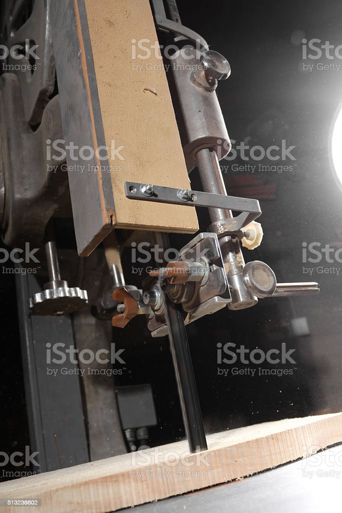 Craftsman cutting a plank of wood with bandsaw stock photo