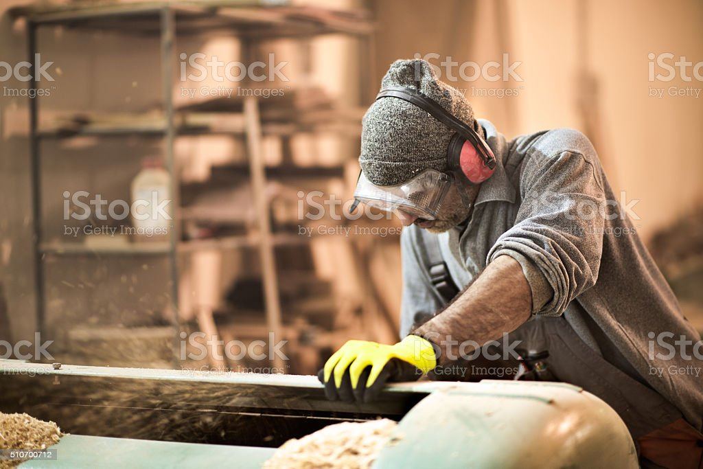 Craftsman cutting planks in the workshop stock photo