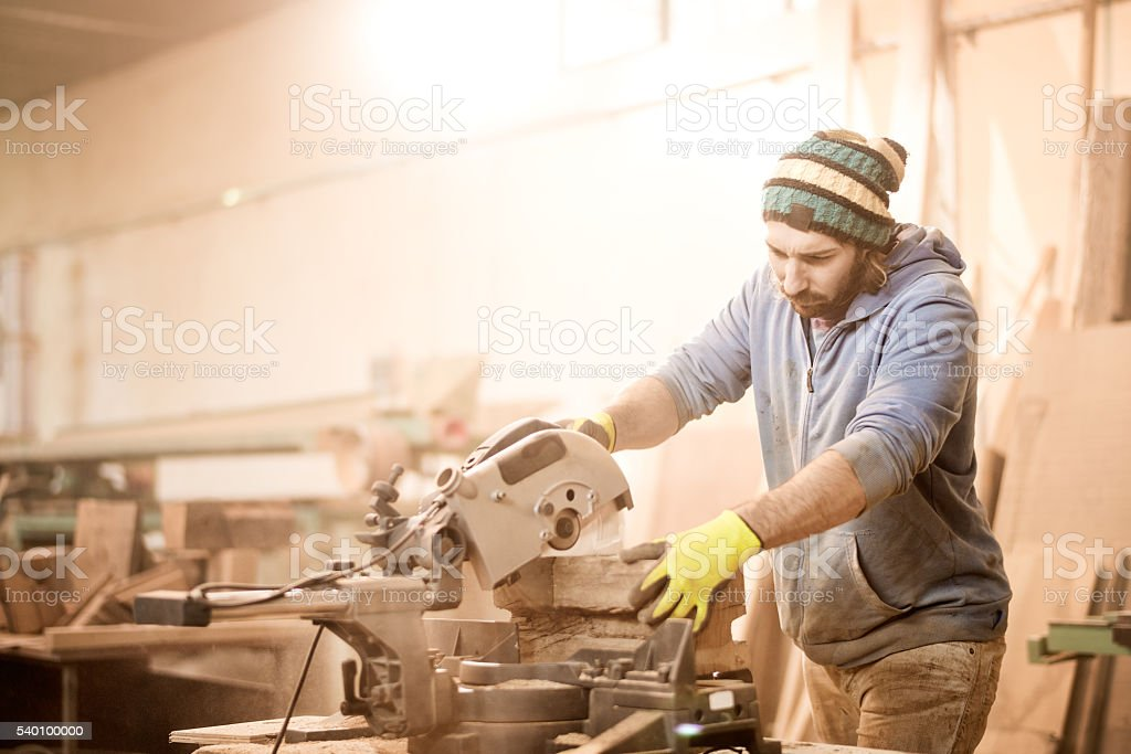 Craftsman cutting wood in workshop stock photo