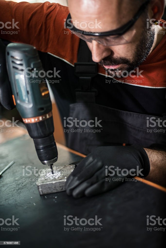 Craftsman drilling in his workshop stock photo