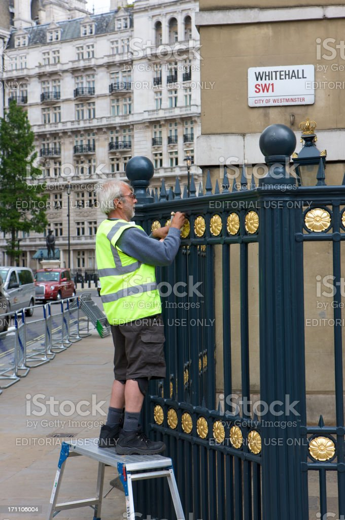 Craftsman gilding railings in preparation for the Queen's diamond jubilee royalty-free stock photo