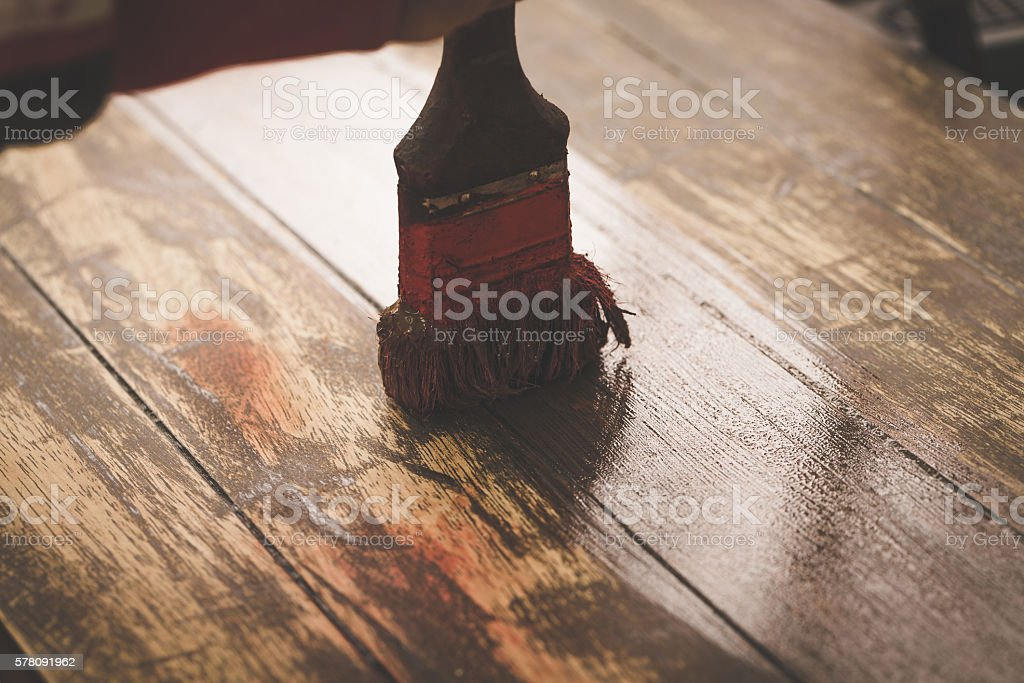 Craftsman hand painting brown color on wooden table stock photo
