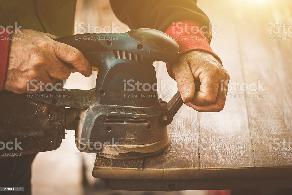Craftsman hands polishing old color from wooden table stock photo