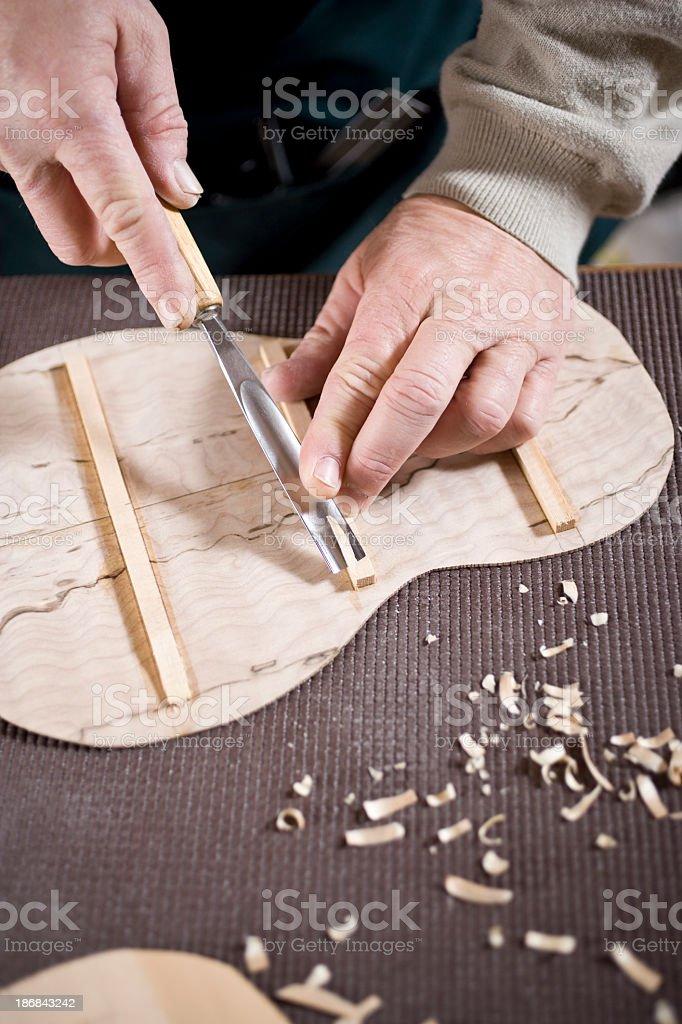 Craftsman in workshop carving violin royalty-free stock photo