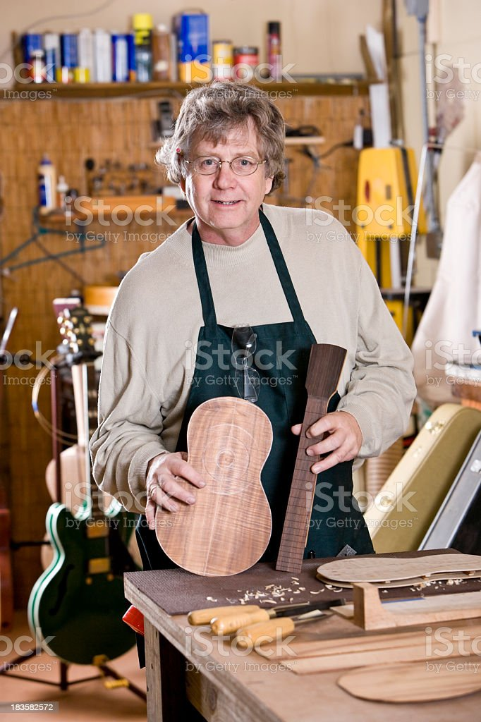 Craftsman in workshop holding unfinished ukulele stock photo