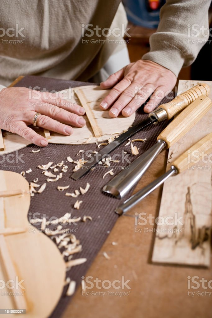 Craftsman in workshop making violin stock photo