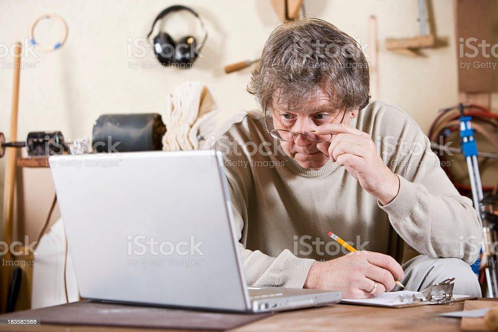 Craftsman in workshop using laptop royalty-free stock photo