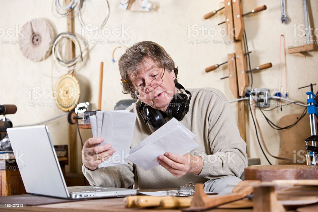 Craftsman in workshop with laptop looking through mail royalty-free stock photo