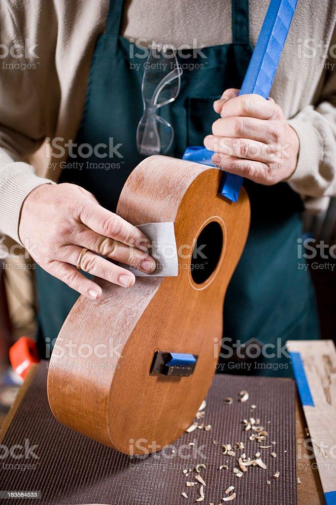 Craftsman in workshop working on ukulele royalty-free stock photo