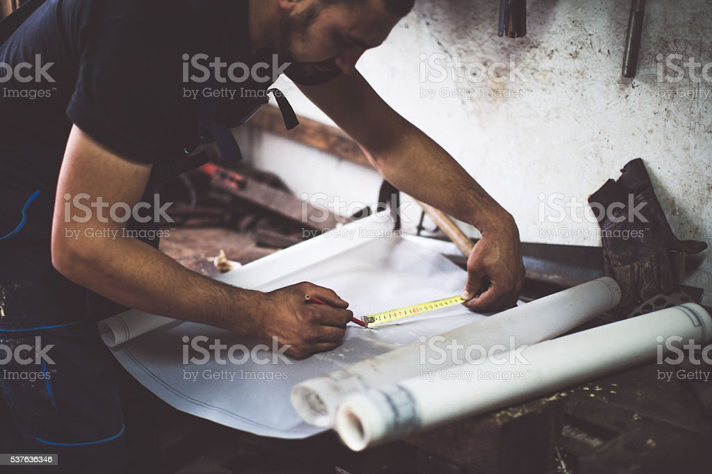 craftsman making measure on his plans stock photo