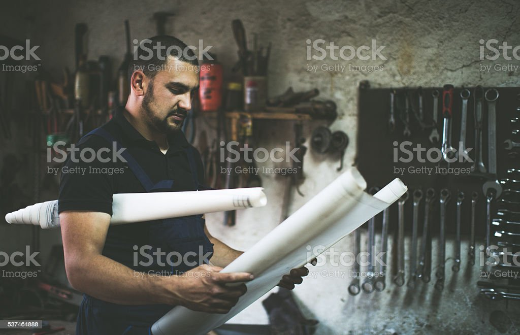 craftsman reading plans on his craft in his workshop stock photo