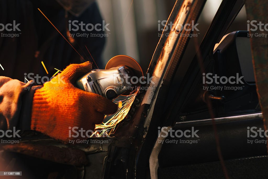 Craftsman repair a car with angle grinder stock photo